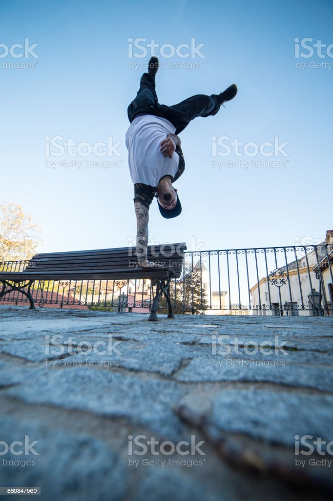 Young man doing handstand on a bench in the street while doing...