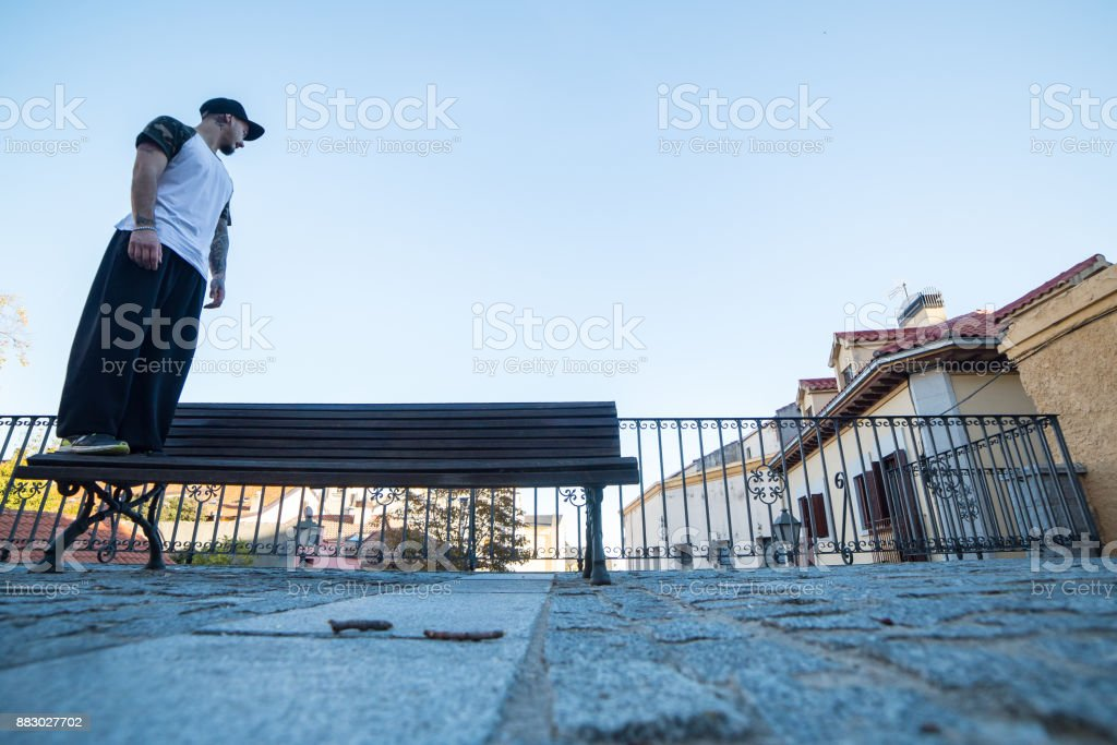 Young man looking at the horizon leaning on a bench in the street...