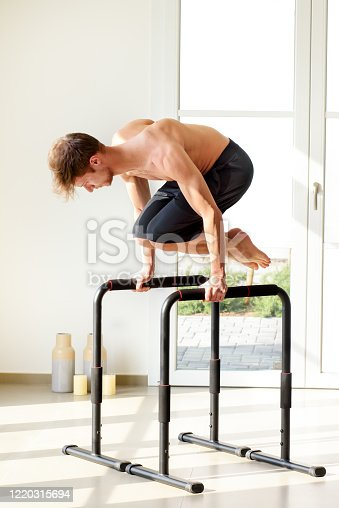 Shirtless muscular man doing planche calisthenics exercise on high on floor bars indoors, with his knees bent
