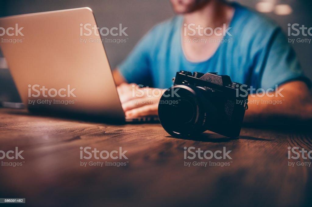 Man doing postproduction of his photos on laptop at night stock photo