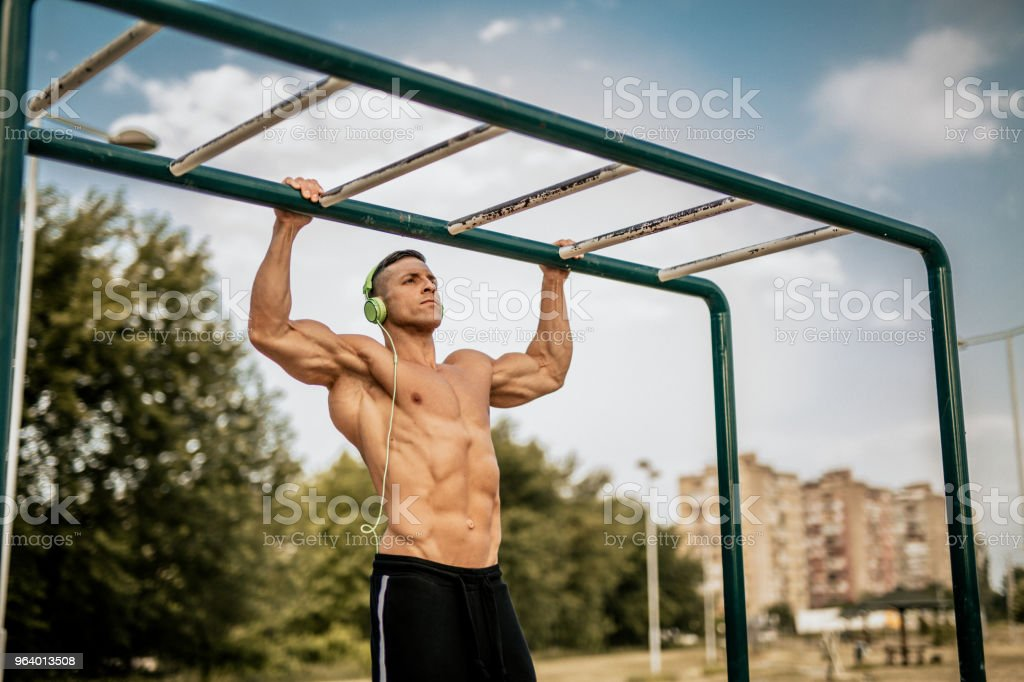 Man doing pull ups in the local park - Royalty-free Adult Stock Photo