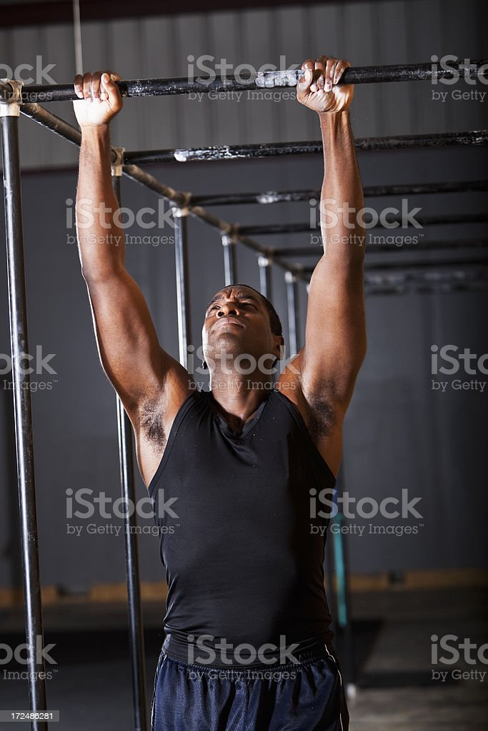 Man doing pull-ups in gym stock photo