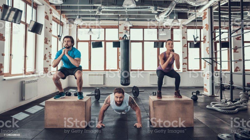 Man Doing Push Ups Guy And Girl Doing Squats Stock Photo