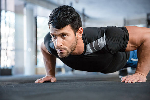 man doing push ups in gym - push up stock photos and pictures