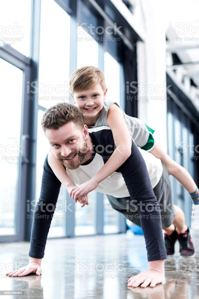Man doing push ups with boy on his back stock photo