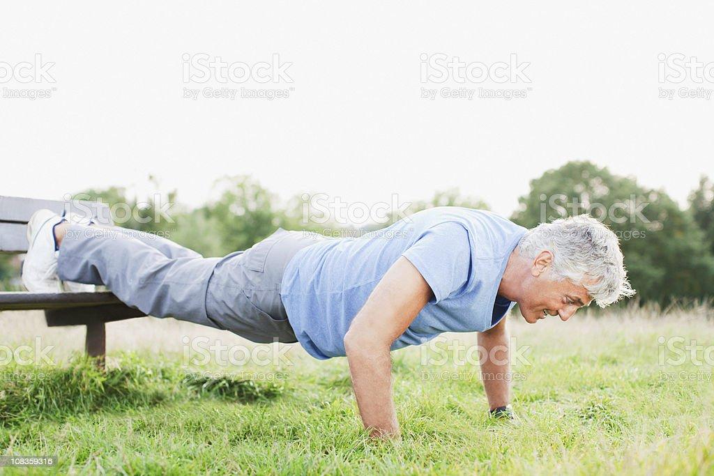 Man doing push-ups in field stock photo