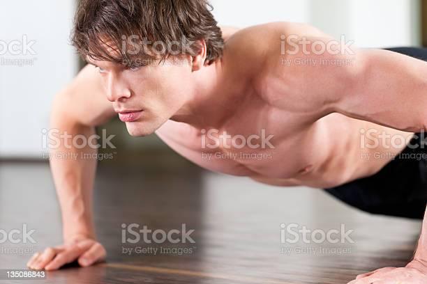 Hombre Haciendo Pushups En El Gimnasio Foto de stock y más banco de imágenes de Actividad