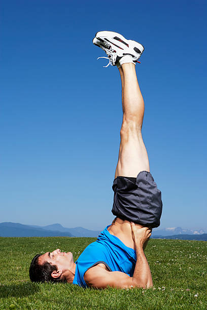 Man doing shoulder stand Man doing shoulder stand shoulder stand stock pictures, royalty-free photos & images