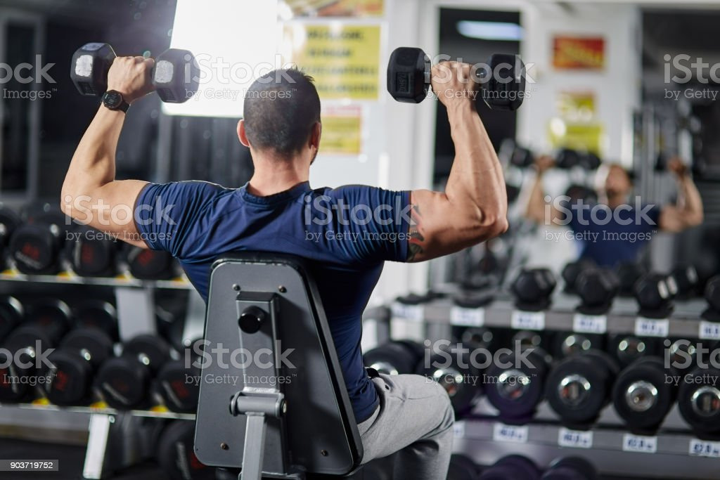 Man doing shoulder workout in the gym stock photo