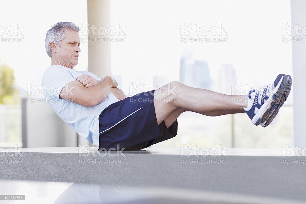 Man doing sit-ups in urban setting royalty-free stock photo