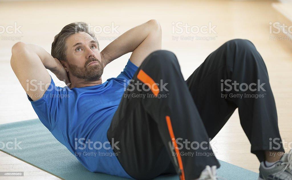 Man Doing Sit-Ups On Exercise Mat stock photo