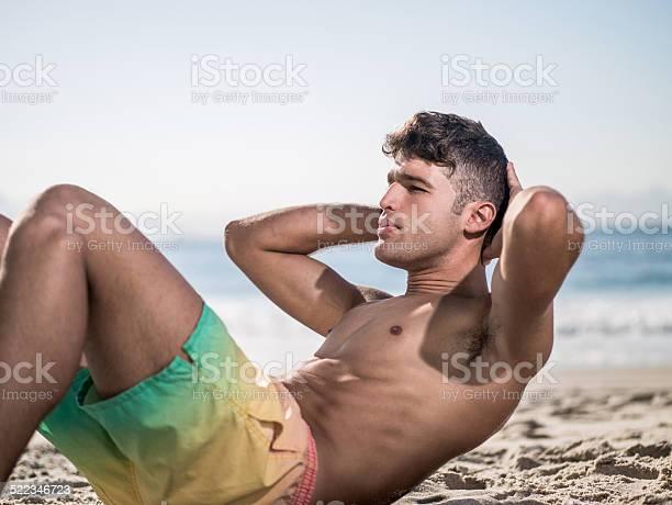 Hombre Haciendo Sit Ups En La Playa Foto de stock y más banco de imágenes de Abdominales