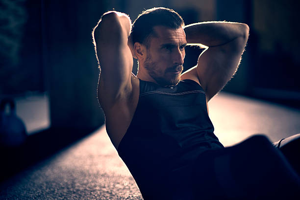 man doing sit-ups - sit ups stock photos and pictures