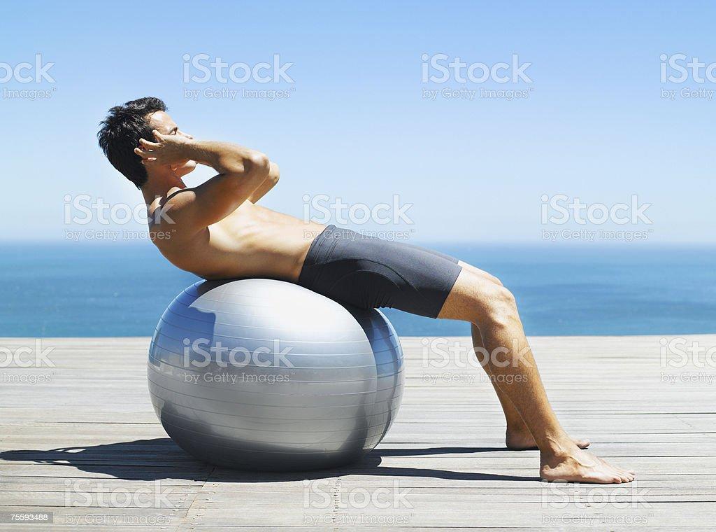 Homem fazendo Abdominais com bola de exercício foto de stock royalty-free