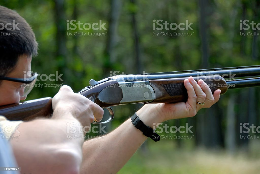 Man doing skeet shooting in the middle of a forest royalty-free stock photo
