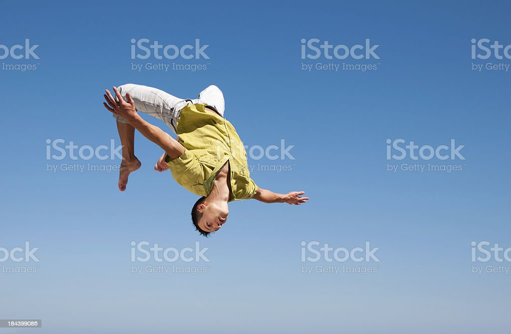 Man doing somersault in the air against blue sky stock photo