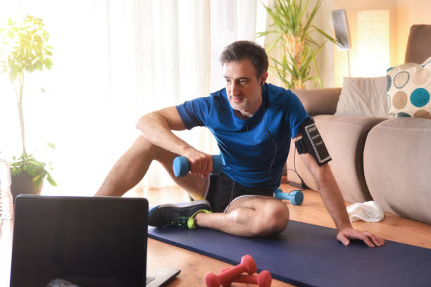 Man doing sports watching videos on a laptop at home stock photo