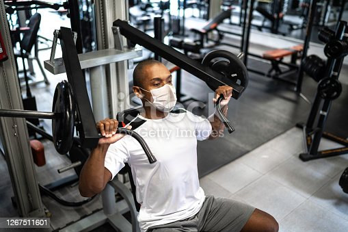 Man doing strength workout exercise in gym with face mask