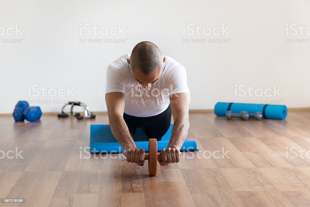 Man doing training with abs roller wheel. stock photo