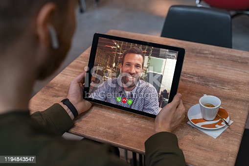 Smiling business partners talking using digital tablet through video call. Back view of man holding tablet in coffee shop while doing video chat calling a friend. Young man and his friend talking to each other through a videocall on a laptop.
