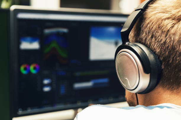 man doing video editing on computer with headphones on stock photo
