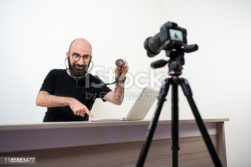957759714istockphoto Man doing vlog about computer repair 1185883477
