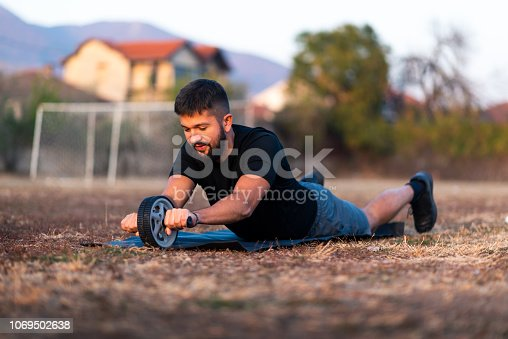 istock Man doing workout with ab roller outdoors 1069502638