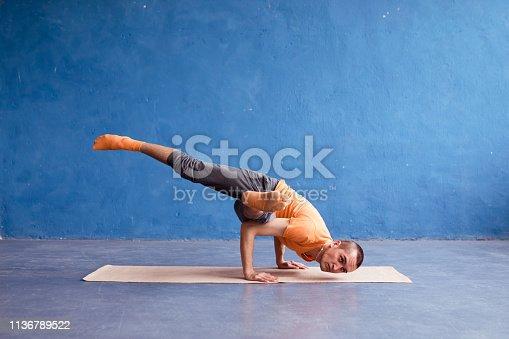 873786782istockphoto A man doing yoga arm balance exercises. Studio shot over loft background. 1136789522