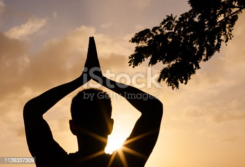 Man doing yoga at the beach during sunset.
