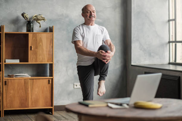 man doing yoga exercise at home using online lesson on notebook. stock photo
