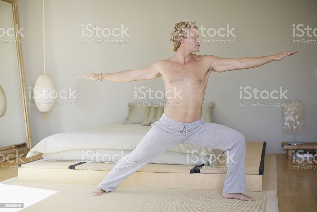 Man doing yoga in bedroom royalty-free stock photo