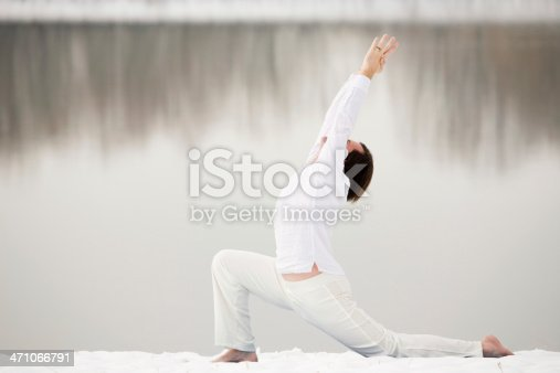 Man in White clothing does Yoga Pose