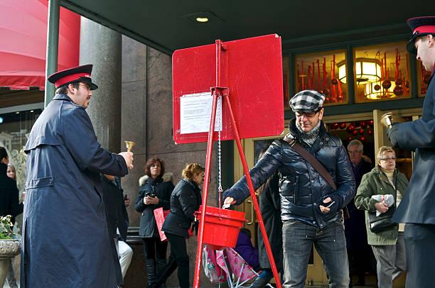 Man donating to Slavation Army Christmas bucket at Macy's, NYC stock photo