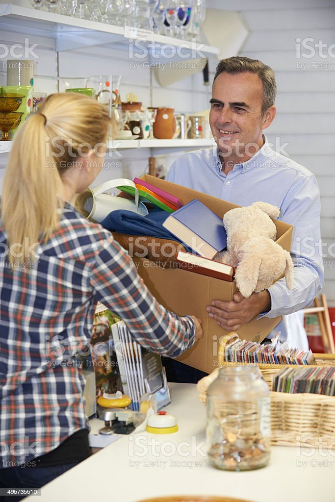 Man Donating Unwanted Items To Charity Shop stock photo