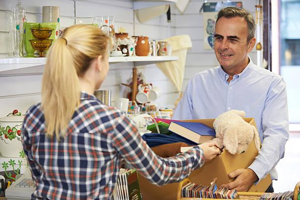 mann, indem sie unerwünschte artikel für einen guten zweck einkaufen - gebrauchte bücher verkaufen stock-fotos und bilder