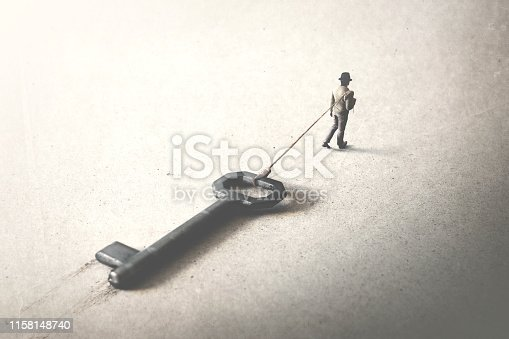 man dragging a big heavy key, access surreal concept