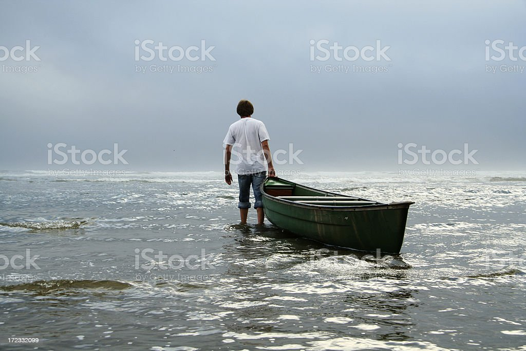 Man Dragging Canoe Boat into Ocean stock photo