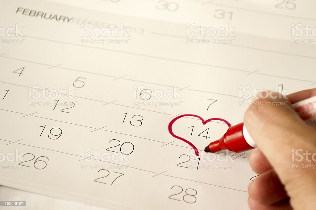Man draw a heart shape in the calendar- february 14th royalty-free stock photo