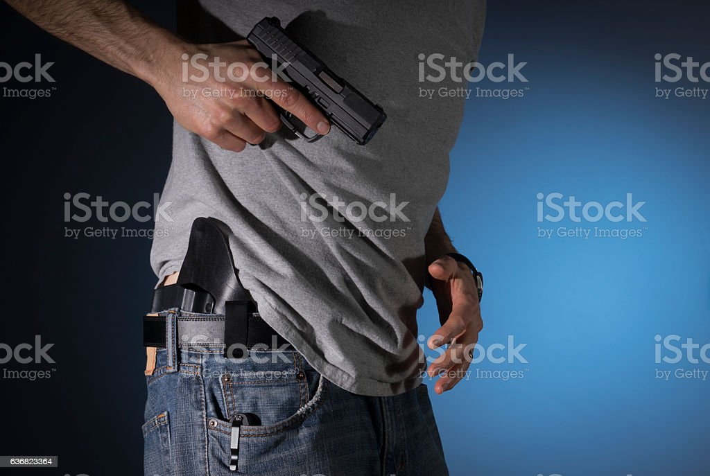 Man drawing a concealed carry pistol from a holster - foto de stock