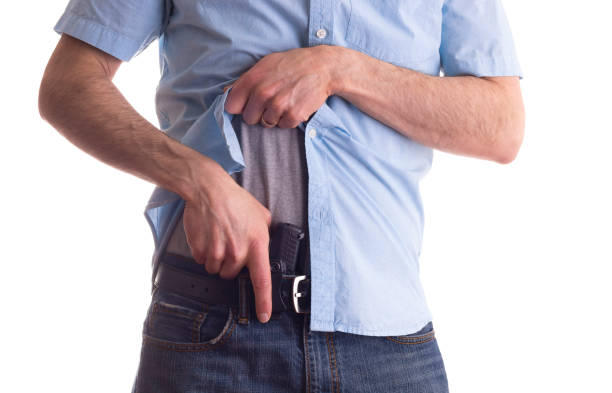 Man drawing a concealed carry pistol from holster stock photo