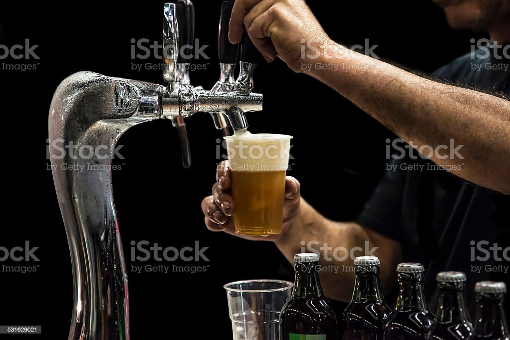 Man drawing beer from tap stock photo