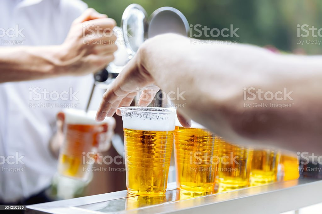 Man drawing beer. Hand takes beer plastic cup stock photo