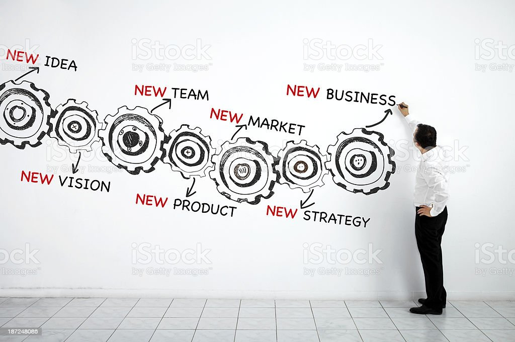 Man drawing business plan made of gears stock photo