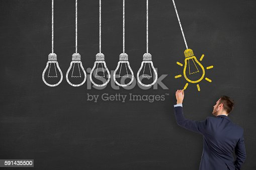 645716366 istock photo Man Drawing Light Bulb on Chalkboard 591435500