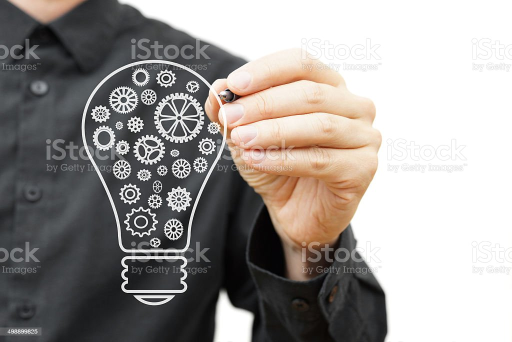 man drawing light bulb with sprockets. Vision,idea, innovation concept stock photo