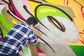 Young caucasian man in plaid shirt drawing street art graffiti.