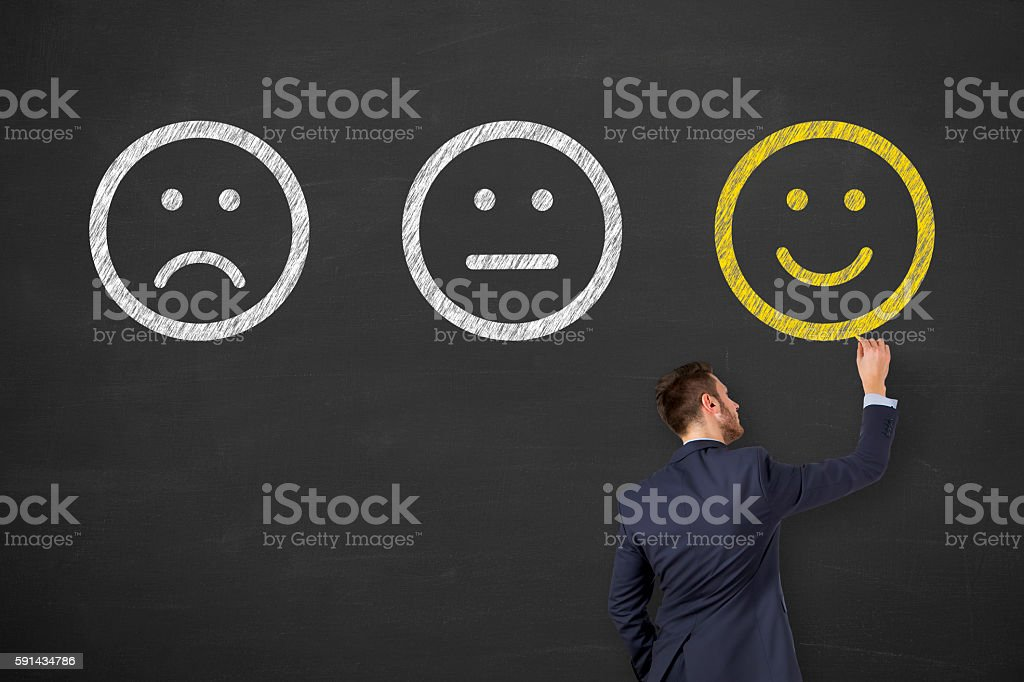 Man Drawing Unhappy and Happy Smileys on Blackboard stock photo