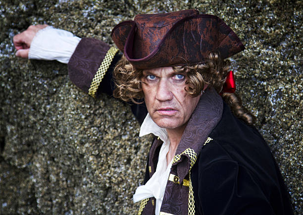 man dressed as a pirate , leaning against rocks - swashbuckler stock photos and pictures