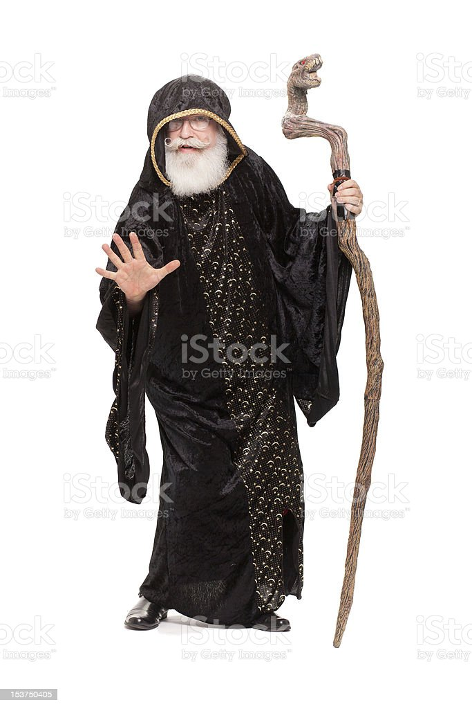 A man dressed as a wizard stands against a white background stock photo
