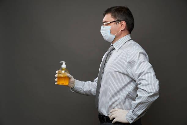 Mann als Geschäftsmann verkleidet, posiert im Studio auf grauem Hintergrund, medizinische Gesichtsmaske und Schutzhandschuhe, Hemd und Krawatte, zeigen Hand desanitizer - Konzept der Quarantäne und Antivirus-Schutz – Foto